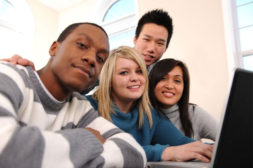 Diverse group of high school students around computer
